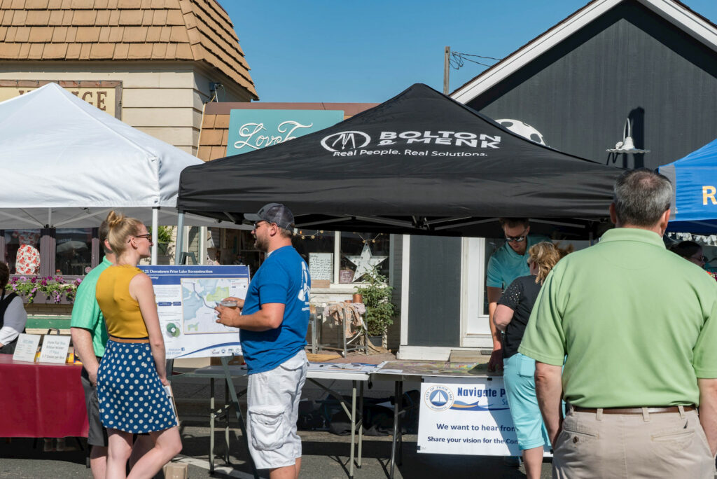 community gathers at farmers market under tent