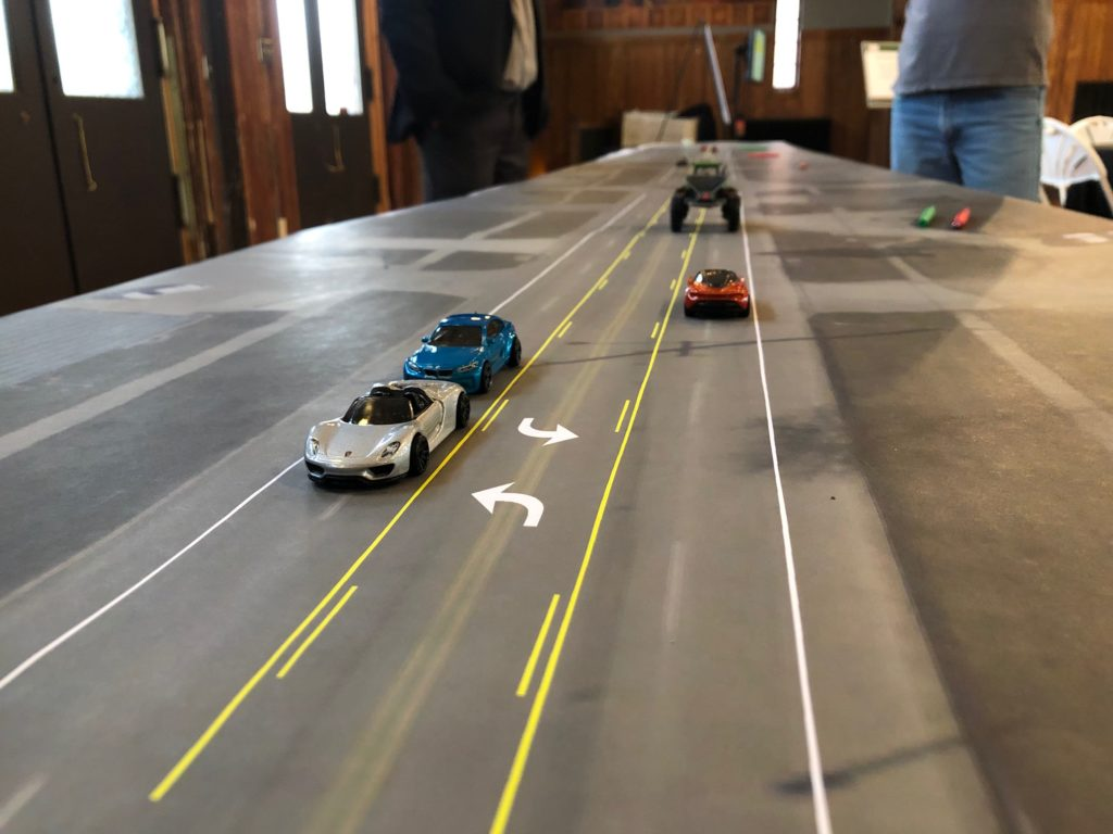 toy cars on a map of the street to demonstrate 3 lane conversion